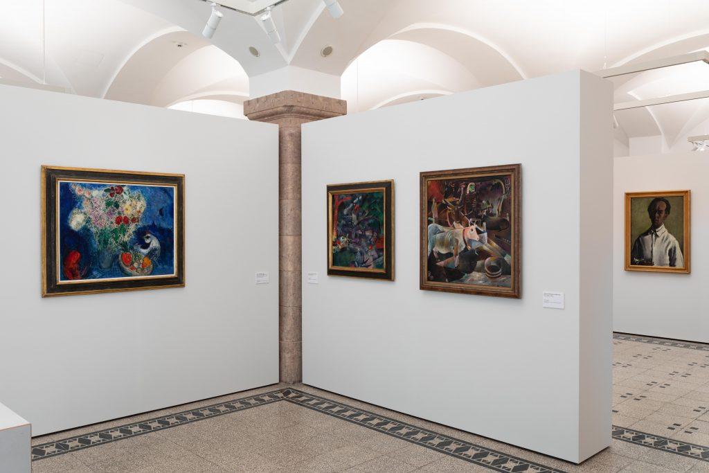 Ausstellungsansicht mit Marc Chagall: Blumenstrauß mit Liebespaar..., 1948-1952; Heinrich Campendonk: Weidende Pferde, 1918; Heinrich Campendonk: Der Kuhstall, 1920 (im Hintergrund: , Foto: Kunstsammlungen Chemnitz/Alexander Meyer
